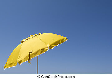 Yellow sun umbrella against the blue sky