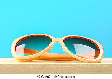 Yellow sunglasses on a wooden shelf on a blue pastel background. Minimalism.
