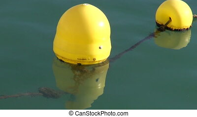 Yellow sunlit buoys in the water - Yellow sunlit buoys in...