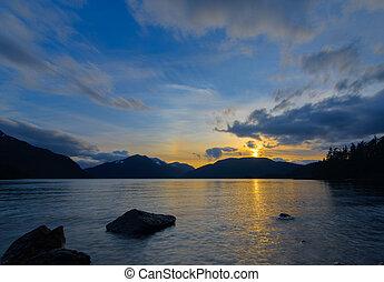 Yellow Sunset Over Mountains Next To Lake