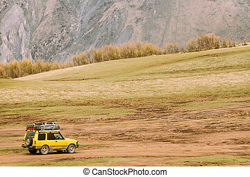 Yellow SUV Car On Off Road In Spring Mountains Landscape. Drive And Travel Concept. Landscape Of Gorge At Spring Season