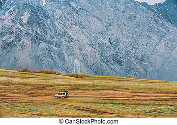 Yellow SUV Car On Off Road In Spring Mountains Landscape. Drive And Travel Concept.