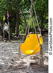 yellow swing on the beach