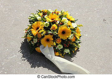 yellow sympathy flowers on a tombstone