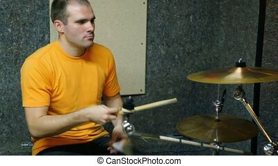 yellow T-shirted drummer playing on dums in recording studio