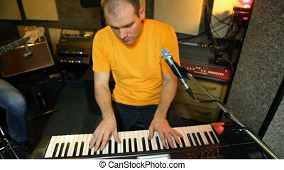 yellow T-shirted keyboard player playing on synthesizer in studio