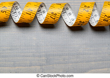 Yellow Tailor measuring tape on wooden table back