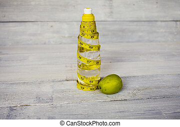 Yellow tape measure and a water bottle and apple on white wooden background . Health concept.