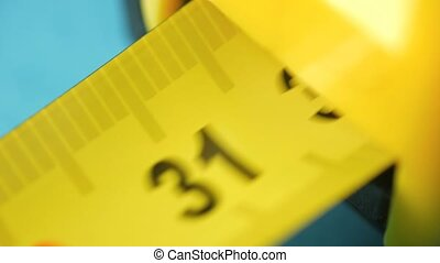 Yellow tape measure, roll of measuring tape.