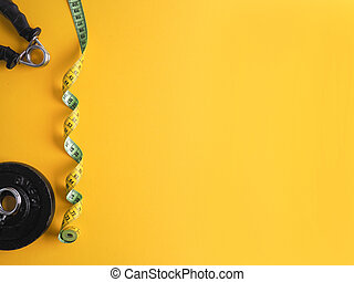 Yellow tape measure with weight plates and a finger dumbbell on a yellow background