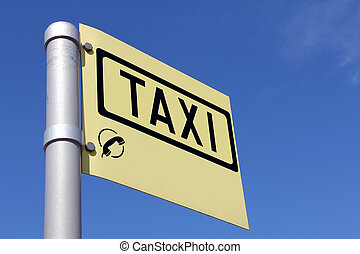 Yellow Taxi Sign against Blue Sky