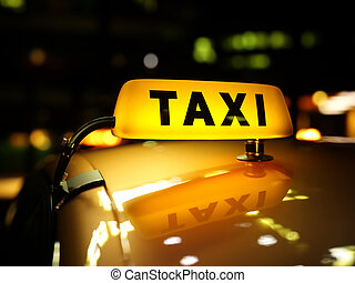 Yellow taxi sign at night