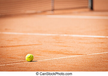 yellow tennis ball on orange sand and white lines