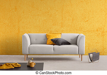 Yellow texture on the wall of elegant living room with stylish couch with pillows, real photo with copy space