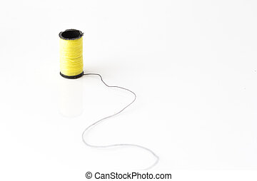 yellow thread loom standing on black thread over white bakcground