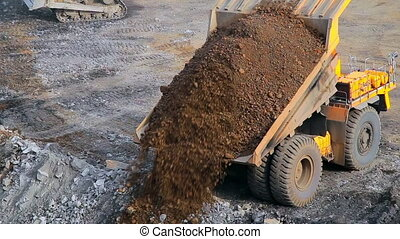 Yellow tipper truck on the quarry unloads earth and gravel