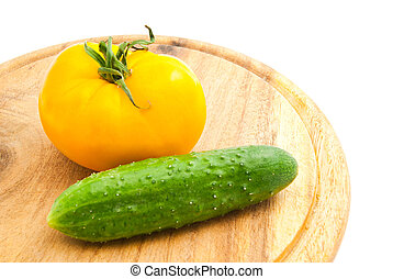 yellow tomato and cucumber on wooden cutting board
