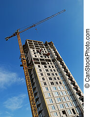 High yellow tower crane builds a multistory (multistoried building) over blue sky. Lower point of view.