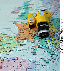 yellow toy camera on the map of Europe and Italy