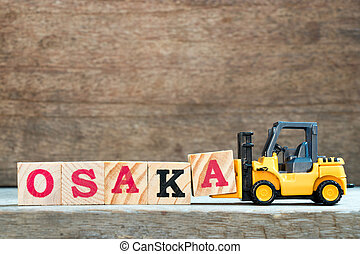 Yellow toy forklift hold letter block A to complete word Osaka on wood background