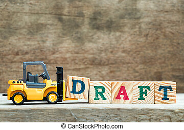 Yellow toy forklift hold letter block D to complete word draft on wood background