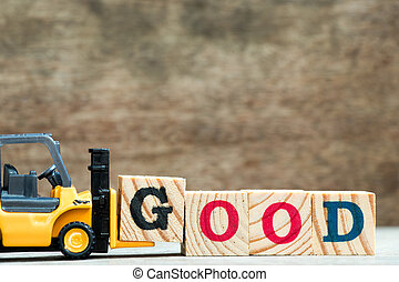 Yellow toy forklift hold letter block G to complete word good on wood background