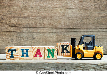 Yellow toy forklift hold letter block K to complete word thank on wood background