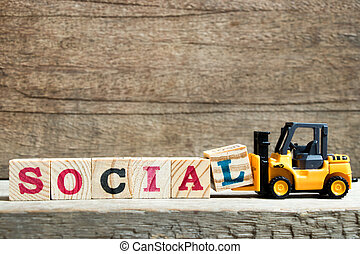 Yellow toy forklift hold letter block L to complete word social on wood background