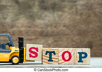 Yellow toy forklift hold letter block S to complete word stop on wood background