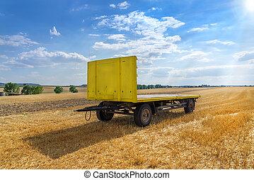 Yellow trailer in a stubble field