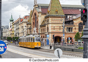Yellow tram and Great market Hall in Budapest, Hungary