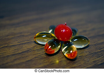Yellow transparent capsules and viburnum berry on wooden background, healthy concept