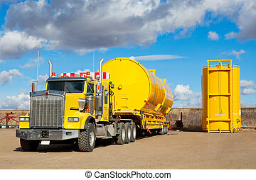 A yellow transport trailer picking up two newly manufactured and coated 400 BBL. oilfield storage tanks.