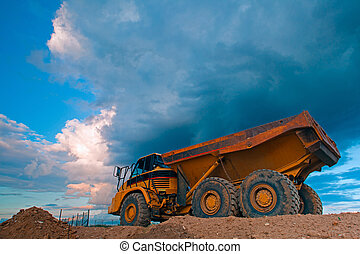 Yellow truck at work site before storm