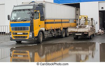 Yellow truck near hangar - The image of two trucks. One big ...