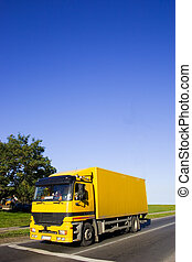 Yellow truck on asphalt road. Large blue sky with place for...