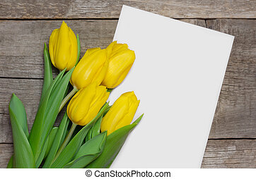 Yellow tulips and white card on wooden background
