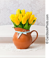 yellow tulips in vase with blue bow