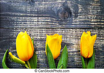 Yellow tulips lie on a black old vintage wooden table background