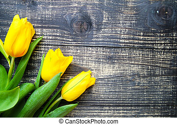 Yellow tulips lie on old vintage table background. Women's Day Concept