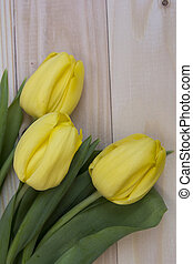 Yellow tulips on a light wooden background.