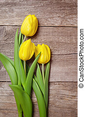Yellow tulips on wooden background.