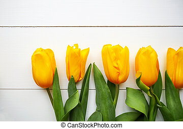 Yellow tulips on wooden table. Top view with copy space