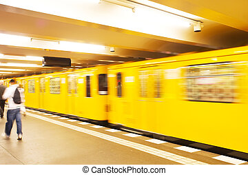 Yellow underground train in motion