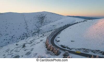 Yellow van driving on winter mountain road, taking big right...