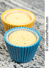 Yellow vanilla cupcakes in porcelain cups above grey marble