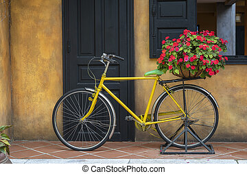 Yellow vintage bike with basket full of flowers next to an old building in Danang, Vietnam