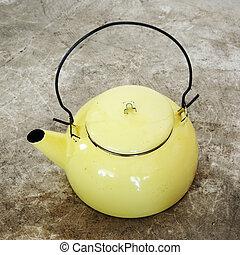 Yellow vintage metallic kettle on cement floor.