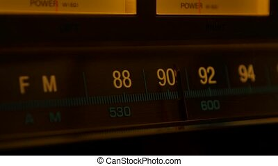 Yellow vintage radio receiver and amplifier with fm scale. Tuning analog radio frequency on scale of the retro receiver. Searching for stations on the old radio. Close up. Slow motion