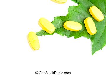 yellow vitamin pills over green leaf